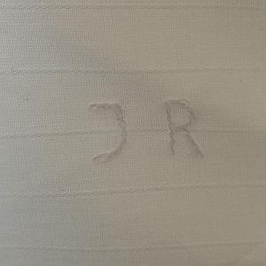 Ik borduurde zijn initialen aan de binnenkant van de schouderpas.