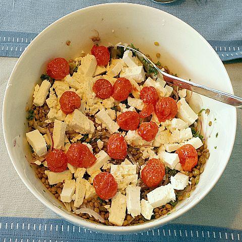 Linzen, dressing van citroensap, beetje olie, knoflook en een theelepel shoarmakruiden. Gehakte peterselie, geschaafde ui, feta en geroosterde tomaatjes.